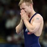 LONDRES. El luchador de Dinamarca Haakan Erik Nyblom (azul) se lamenta tras perder la medalla de bronce tras enfrentar a Peter Modos de Hungría, durante un combate de lucha grecorromana masculina en la categoría de 55 kilos de los Juegos Olímpicos de Londres 2012. Foto: EFE