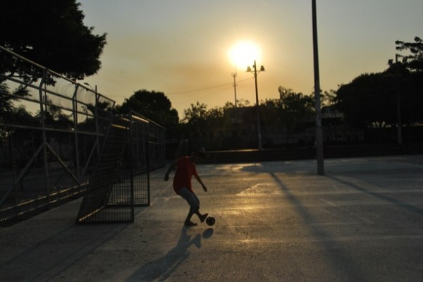 Un joven juega con una pelota en el parque Puerto Liza, en Venezuela y la Octava, en el suroeste de Guayaquil.