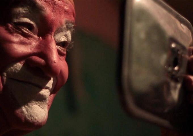 Carlos Astudillo se mira al espejo y sonríe mientras continúa con el maquillaje del payaso Fresco Solo.