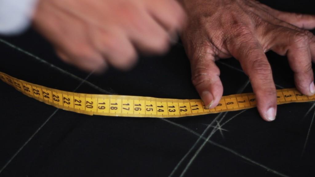 Fernando Yagual marca con tiza una tela donde elaborará un traje.