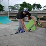 Allan García coloca cera en una de las puntas de las rampas de skateboarding que estaba resbalosa por la lluvia.