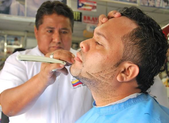 Aurelio Bohórquez da forma a la barba y patillas de Pedro Morán en la Peluquería Mi Alborada.